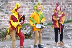 Members of Hauvoy dressed as jesters and playing the medieval bagpipes