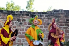 Members of Hauvoy dressed as jesters and playing medieval music